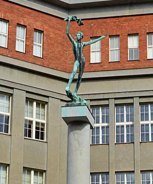 Bronzová socha Vítěze před od Jana Štursy před vchodem do gymnázia J. K. Tyla v Hradci Králové
